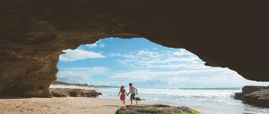 A couple inside a cave on a beach