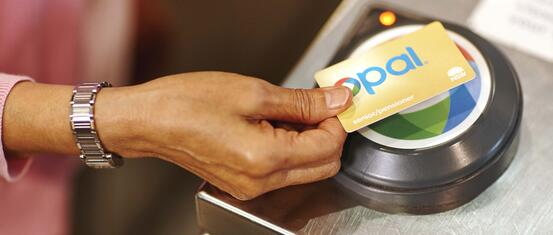 female hand tapping gold senior pensioner opal card